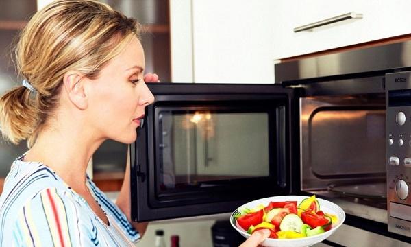 Девушка ставит тарелку в микроволновку