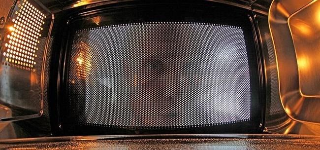 Мужчина заглядывает в микроволновку